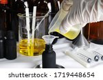 Small photo of beaker with fragrance and essential oil inside on table with many bottles of essential oil is poured for testing scent by a perfumer in a lap before making air room freshener and scented candle
