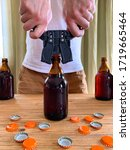 Small photo of Craft beer brewing at home, man closes brown glass beer bottles with plastic capper on wooden table with orange crown caps. Vertical image