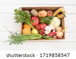 Small photo of vegetables and fruits are in a cardboard box on a white wooden background. Flat Lay, Copy Space. Fruit storage box. Food delivery