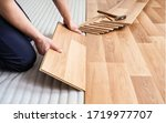 Small photo of Installing laminated floor, detail on man hands holding wooden tile, over white foam base layer, small pile with more tiles background