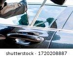 Small photo of Man thief robbing car on parking.Bandit burglar in criminal scene opening and braking car window on force