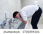 Small photo of Muslim man taking ablution for prayer. Islamic Religious Rite Ceremony Of Ablution. Young Muslim man perform ablution (wudhu) before prayer.