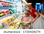 Small photo of Shopping with kids during virus outbreak. Mother and child wearing surgical face mask buying fruit in supermarket. Mom and little boy buy fresh vegetable in grocery store. Family in shop.