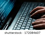 Stock photo hacker using laptop lots of digits on the computer screen 172084607