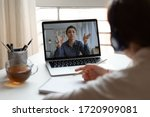 Small photo of Back view of millennial girl in headphones listen watch online training or course on laptop, female employee make notes engaged in webcam conference or briefing with colleague, have web meeting at