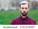 Small photo of Portrait of religious young Jewish guy in traditional jewish male headdress, hat, boom, or yiddish on his head. Serious Israel man with beard looking at camera outdoors. Copy space, place for text.