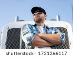 Confident semi truck driver wearing plaid shirt and black baseball cap  stands with arms crossed in front of big rig. Portrait of professional looking trucker. Blue collar jobs in transportation.  - stock photo