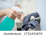 Small photo of Woman house keeper cleaning a dirty stainless door knob in toilet. Maid spraying liquid cleaning solution on the dirty door knob handle in toilet and using micro fabric wipe on door knob surface.