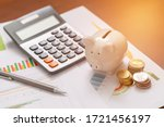 Small photo of Piggy bank and coins for saving money with business stuff, Business and finance concept