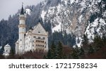 The Neuschwanstein. Romantic castle on the background of snow-capped Alpine mountains of pines and trees.Castle of king of Bavaria near the town of Fussen and Hohenschwangau castle.