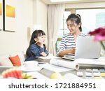 Small photo of young asian designer mother working from home using laptop computer while taking care of daughter (artwork in background digitally altered)