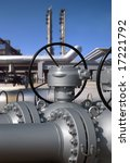 Detailed view of petrochemical pipes with a refinery on background. - stock photo