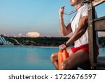 Small photo of Closeup portrait of an unrecognizable lifeguard with a whistle in his hands. Copy space. Lifeguards at the resort.
