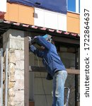 Small photo of A man performing welding work with a metal frame of an annex to a store