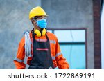 Electrician wearing protective mask to Protect Against Covid-19 and checking production process at the construction site,Engineer,Construction concept,Coronavirus has turned into a global emergency. - stock photo