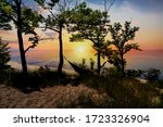 The silhouette of Indiana Dunes State Park landscape overlooking Lake Michigan at sunset near Porter, Indiana, USA.