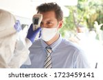 Disease control experts  use an Infrared thermometer equipment to check the temperature on the forehead and use alcohol gel to screen the patients addicted to Covid before entering the building. - stock photo