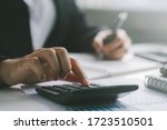 Small photo of Close up businessman hand using calculator and writing make note with calculate about finance accounting.finance accounting concept