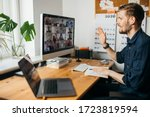 Small photo of Young man having video conferencing call via computer. Working remotely managing team virtual call Stay at home and work from home.Virtual House party Home office computer desk.