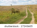 rural dirty road under blue sky - stock photo