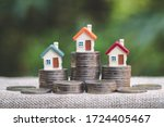 Small photo of Mini house on stack of coins, Concept of Investment property, Investment risk and uncertainty in the real estate housing market.