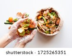 Small photo of Organic food waste in paper bag and in hands on white background top view. Vegetable peelings and food leftovers ready to compost. Environmentally responsible behavior, recycling waste concept.