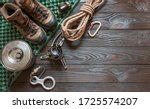 climbing equipment: rope, trekking shoes, flashlight, carabiners, burner, saucepan, tourist rug and other set on dark wooden background, top view with empty space for text. Travel concept.