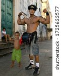 Small photo of Salvador de Bahia/Brazil - May, 10 2010: Little boy and big adult bodybuilder staying on the street in position shows biceps. The boy really happy and tray to be like a strong man. Funny skit