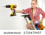 Young determinated woman using drill doing home renovation. Female construction worker having driller tool drilling wall. - stock photo