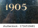 """1905"" carved into a black, polished stone and painted in gold – a detail of an inscription produced that year. Some of the paint has withered away"