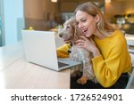 Small photo of Portrait of beautiful blogger babe with surprised face holding her adorable puppy and using laptop while watching comedy.