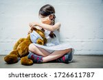 Young girl wearing a mask placing a mask on her teddy bear during covid-19 pandemic.  - stock photo