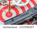 Small photo of Red dart hits in the center number 10 of a target with a pair of handcuff and a pistol, depicting a person under duress got a command or order to gain success or goal by using any methods even illegal