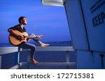 man playing guitar at dusk beach | Shutterstock . vector #172715381