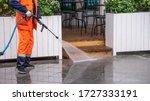 Worker Washes The Sidewalk In...