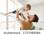 Cheerful Young Father Holding...