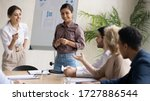 Small photo of Diverse happy colleagues flip charts presentation new project in boardroom at company meeting. Indian and caucasian businesswomen auditors speaks with partners about business using board and graphs.