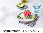 Small photo of Tuna tartare tartar with avocado and quinoa. gourmet presentation with culinary ring on wite plate.
