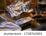 Small photo of Various food dishes covered in tin foil at a party or Thanksgiving