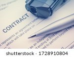 Small photo of Signing a contract under pressure or under duress, business law concept : Pen and a gun or a pistol on a legal contract form, depicting a contract was signed by a coerced or forced person at gunpoint