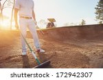 golfer raking bunker in early...