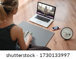 Small photo of Yoga teacher conducting virtual class at home on a video conference. Young beautiful woman doing an online yoga class in her living room with laptop. Home fitness and workout concept