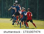 Small photo of Soccer players heading the ball in competition. Football adult game. Players in two teams compete for the ball. Footballers jumping high on the grass pitch
