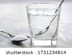 Small photo of Salt water in a glass cup and salt in a teaspoon. Salt water has high level of minerals and salt water gargle helps in removing of cold and sore throat