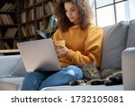 Small photo of Young hispanic latin ethnic teen girl relaxing sit on comfortable sofa with cute pet cat watching remote education webinar class, movie series on laptop drinking warm tea in cozy sunny living room.