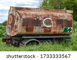 old and rusty fuel tanker trailer abandoned in a field - stock photo
