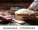 Hands Holding A Wooden Bowl Of...