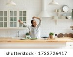 Small photo of Happy millennial girl preparing healthy breakfast having fun in bright modern kitchen at home, overjoyed young woman cooking in new house or apartment feel excited moving relocating to own dwelling