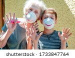 Small photo of Happy laughing grandmother with grandchild in a respiratory masks plays together near house. Family fun. Stay at home. Drawing a smile on protective masks. Quarantin, isolated. Coronavirus covid-19.
