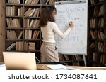Small photo of Female latin indian math school teacher or student writing equation on whiteboard in classroom. Virtual live remote teaching concept. Distance online education exam preparation elearning course.